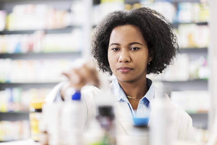 African American pharmacist selecting pill bottles
